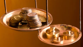 Coins on a scale weight. Vintage scale wheights outweigh coins on an old balance Stock Image