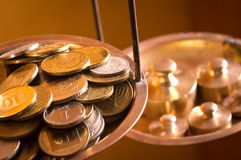 Coins on a scale weight. Vintage scale wheights outweigh coins on an old balance Stock Photos