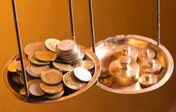 Coins on a scale weight. Vintage scale wheights outweigh coins on an old balance Royalty Free Stock Photo