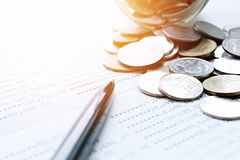 Coins scattered from glass jar, pen and savings account passbook or financial statement on office desk table. Business, finance, saving money or investment Stock Photo