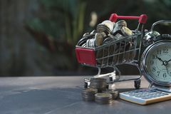Coins in shopping cart with money stack step growing money Royalty Free Stock Photo