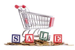 Coins, shopping cart and word SALE Stock Images