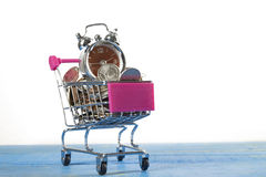 Coins and shopping trolley with clock Stock Images