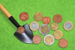 Coins, shovel on a green background. Royalty Free Stock Photography