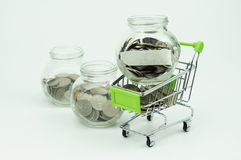 Coins in small container and shopping cart- financial concept. Coins in small container and shopping cart with blank label - financial concept stock photography