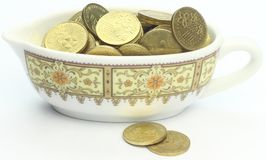 Coins in a small saucer bowl Stock Images