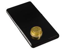 Coins on the smartphone. Few coins on the black glossy screen of smartphone Stock Photos