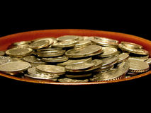 Coins in soup plate. Silver coins from all over the world in a soup plate, isolated on black background Stock Photography