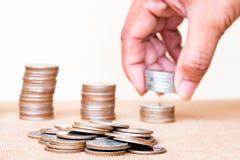 coins sparande för stapel för begreppshandpengar skyddande Myntet och det suddiga slutet fingrar upp hållstac Royaltyfri Fotografi