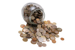 Coins spilled from a glass jar . Royalty Free Stock Images