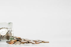 Coins spilled from glass jar, with copy space on white background Stock Image