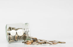 Coins spilled from glass jar, with copy space on white background Stock Images