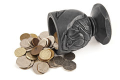 Coins spilling a cup of coal Royalty Free Stock Photos