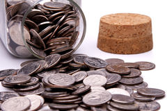 Coins Spilling From a Jar Stock Photos