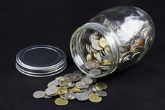 Coins Spilling from a Jar Royalty Free Stock Photography