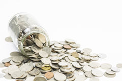 Coins spilling from a money jar Royalty Free Stock Photo