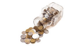 Coins spilling from a money jar Stock Photo