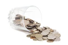 Coins spilling out from a glass. Isolated stock photo