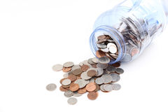 Coins spilling out of a jar Royalty Free Stock Image