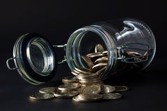 Coins spilling out jar Royalty Free Stock Photography