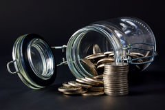 Coins spilling out jar Royalty Free Stock Image
