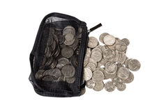 Coins Spilling Out Of Purse Isolated. Horizontal shot of a black net coin purse with silver coins spilling out.  Isolated on a white background Royalty Free Stock Image