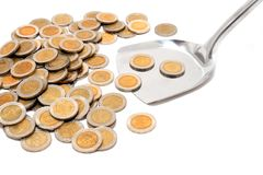 Coins and the spoon in a plate on a white backgrou Royalty Free Stock Photos