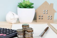 Free Coins Stack And Calculator In Front Of Wood House Model And Piggy Bank Royalty Free Stock Image - 98765216