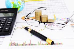 Coins stack and eyeglasses and fountain pen and calculator for stock investment concept royalty free stock images