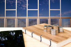 Coins stack on handmade book with tablet on wood table with building reflect sky background. Stock Photography