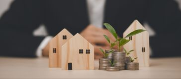 Coins stack and leaf with line graphic business connect with Mini wood house model from model on wood table, Planning buy Real Es