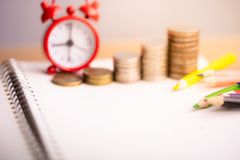 Coins stack and red alarm clock with Colored pencils on notebook. stock image