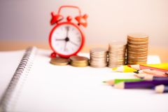 Coins stack and red alarm clock with Colored pencils on notebook. stock photography