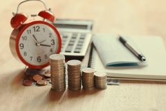 Coins stack and red alarm clock with pen, calculator and notebo. Ok for banking and finance concept Royalty Free Stock Photo