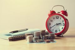 Coins stack and red alarm clock with pen, calculator and notebo Stock Photo