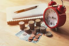 Coins stack and red alarm clock with pen, calculator and notebo. Ok for banking and finance concept Stock Images