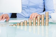 Coins stacked on desk in front of businesswoman Stock Photography