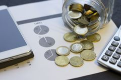 Coins stacked on each other in different positions. Next to calculator and phone. Money and saving concept Stock Photo