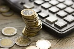 Coins stacked on each other in different positions. Euro coins and calculator. Euro money. Euro currency. Coins stacked on each other in different positions Stock Image