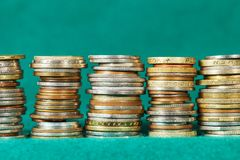 Coins stacked in five stacks. Can be seen against the background of green fabric Stock Image