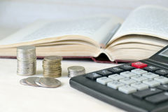 Coins stacked pile, calculator, open book. Calculation of financial stability and business development Stock Photos