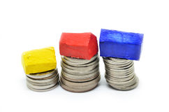 Coins stacked up in piles with color house Royalty Free Stock Photo