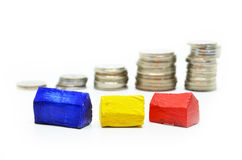 Coins Stacked up in piles with color house Stock Photos