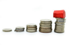 Coins stacked up in piles with color house Stock Photography