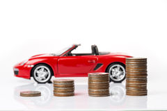 Coins stacking up in graph shape with red sport car in backgroun. D meaning for making money Royalty Free Stock Image