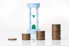 Coins stacking up in graph shape with sandclock in the backgroun Stock Images