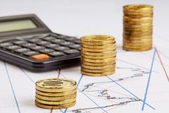 Coins stocks rising, calculator on the financial charts Royalty Free Stock Images