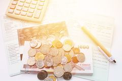 Coins, Thai money, pen, calculator and savings account passbook on white background Stock Images
