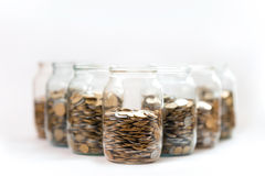 Coins in a three glass jars against Royalty Free Stock Photo
