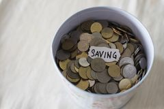 Coins in tin with a notes written by the word `saving`. Stock Image